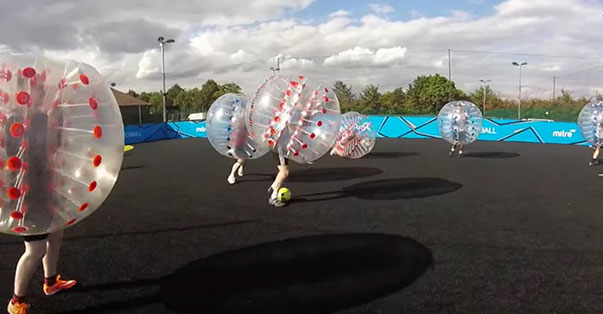 Employee inside a zorb playing bubble football at a london venue