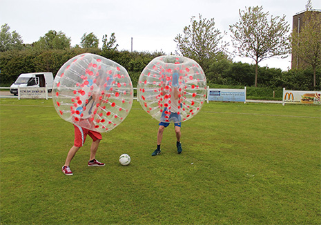 two people playing bubble football in a UK field