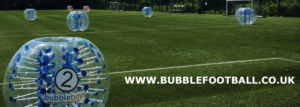 5 people playing bubble football on a grass field in london