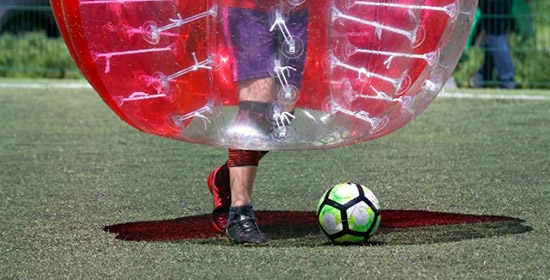 man kicking big red inflated bubble ball